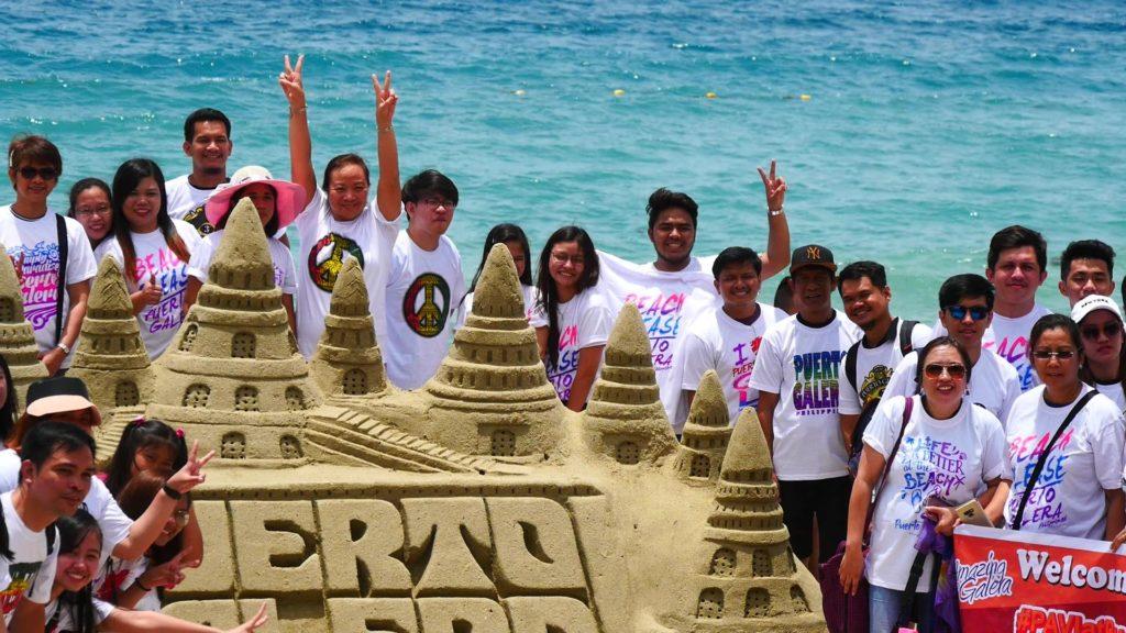 ビーチの砂彫刻の前で記念写真を撮る団体の人たち