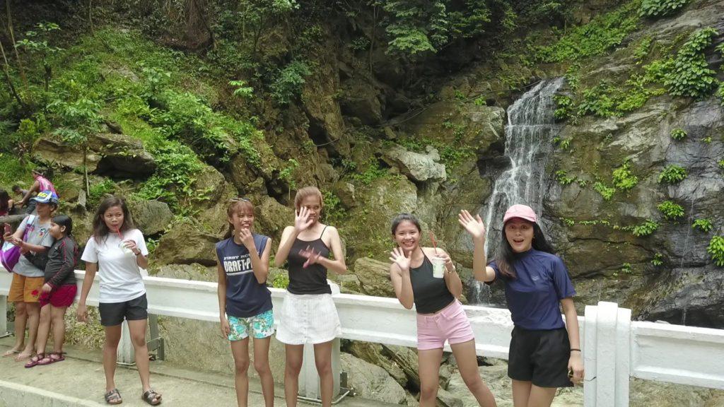 タマラオの滝の前でポーズをとる女学生たち