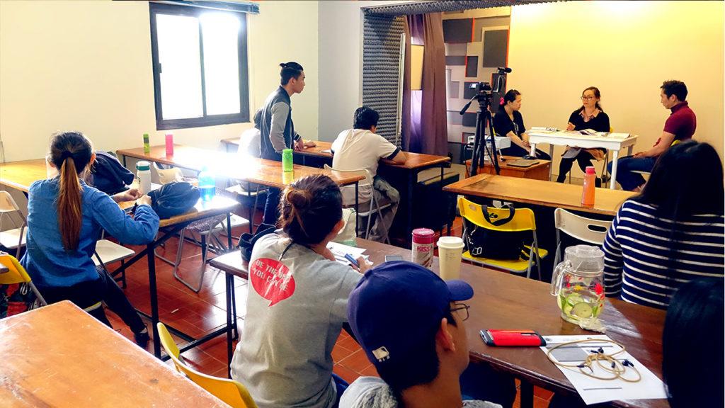 大勢の先生と学生に囲まれながら就職面接模擬試験を受けているMONOLの学生