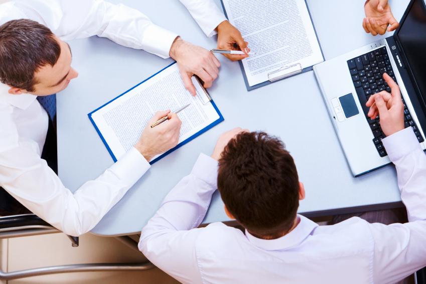 パソコンをはさんだビジネス会議の場