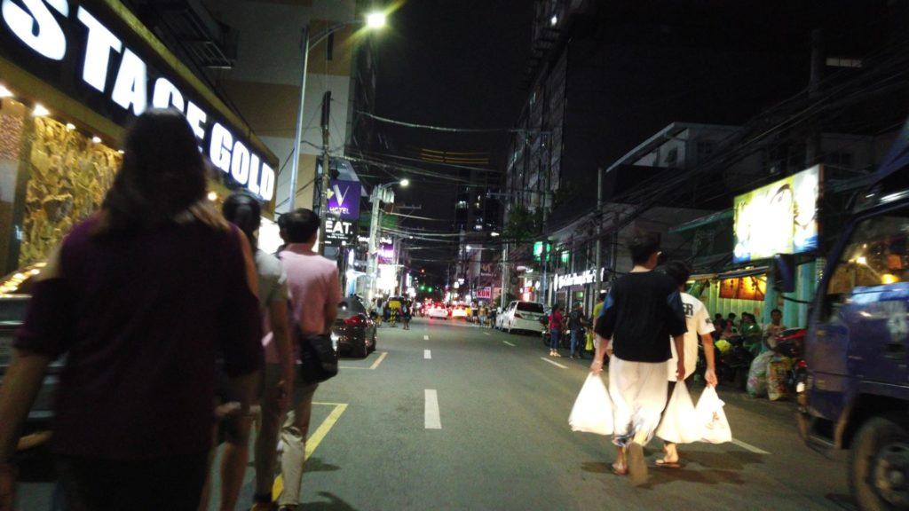 アドリアティコ通りでスーパーのビニール袋を持った買い物帰りの若い韓国人男女グループ