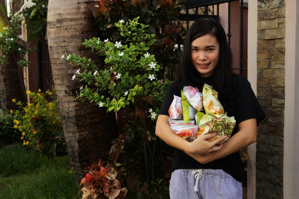 たくさんのお菓子の袋を腕に抱えるフィリピン人家政婦ジェニー