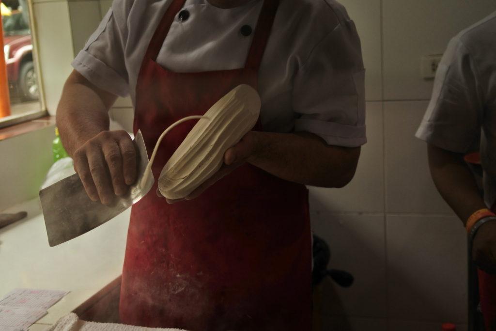 料理人が包丁で麺を切っている