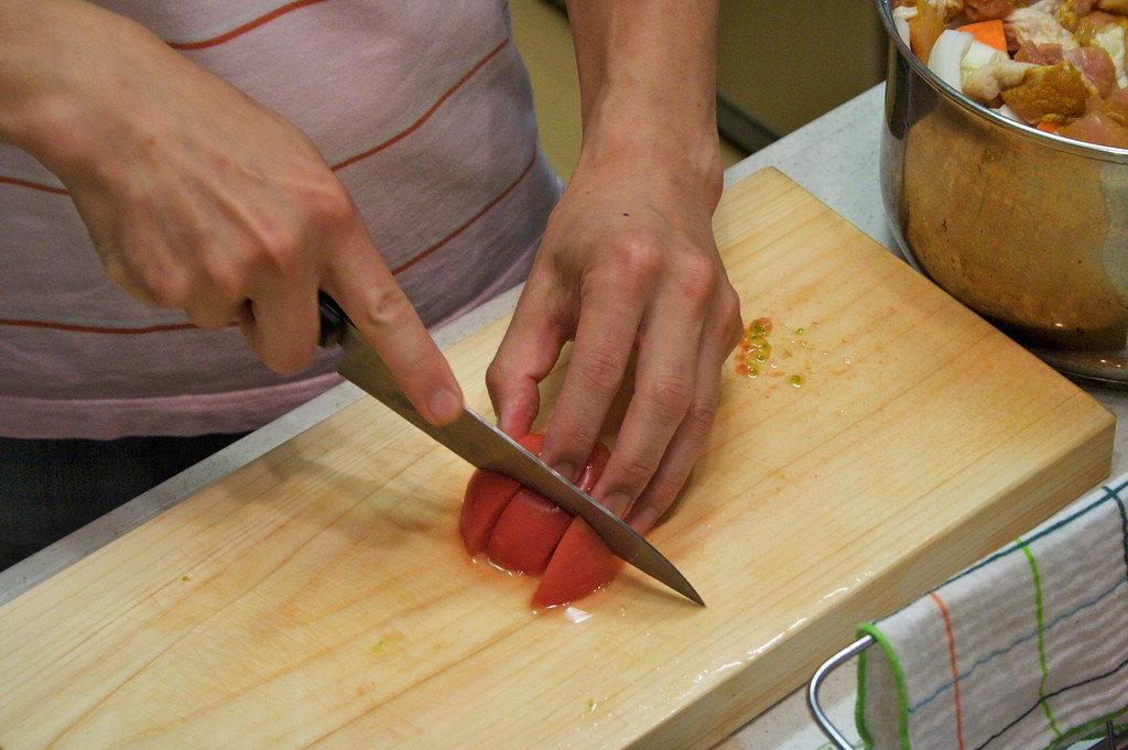まな板の上でトマトをカットする様子
