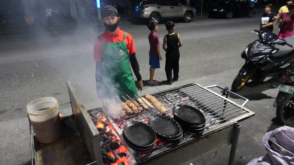 炭火で食材をグリルする店員