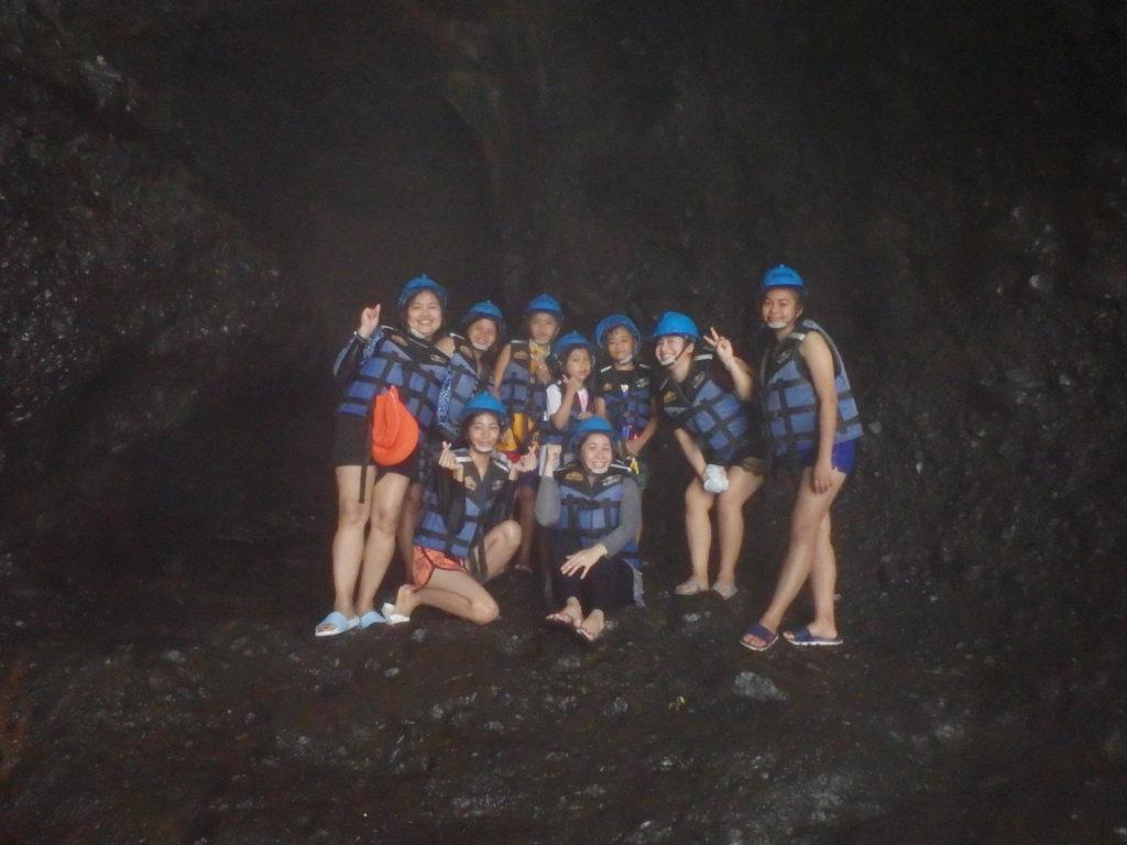 滝の裏の空洞で写真ポーズを取る観光客たち
