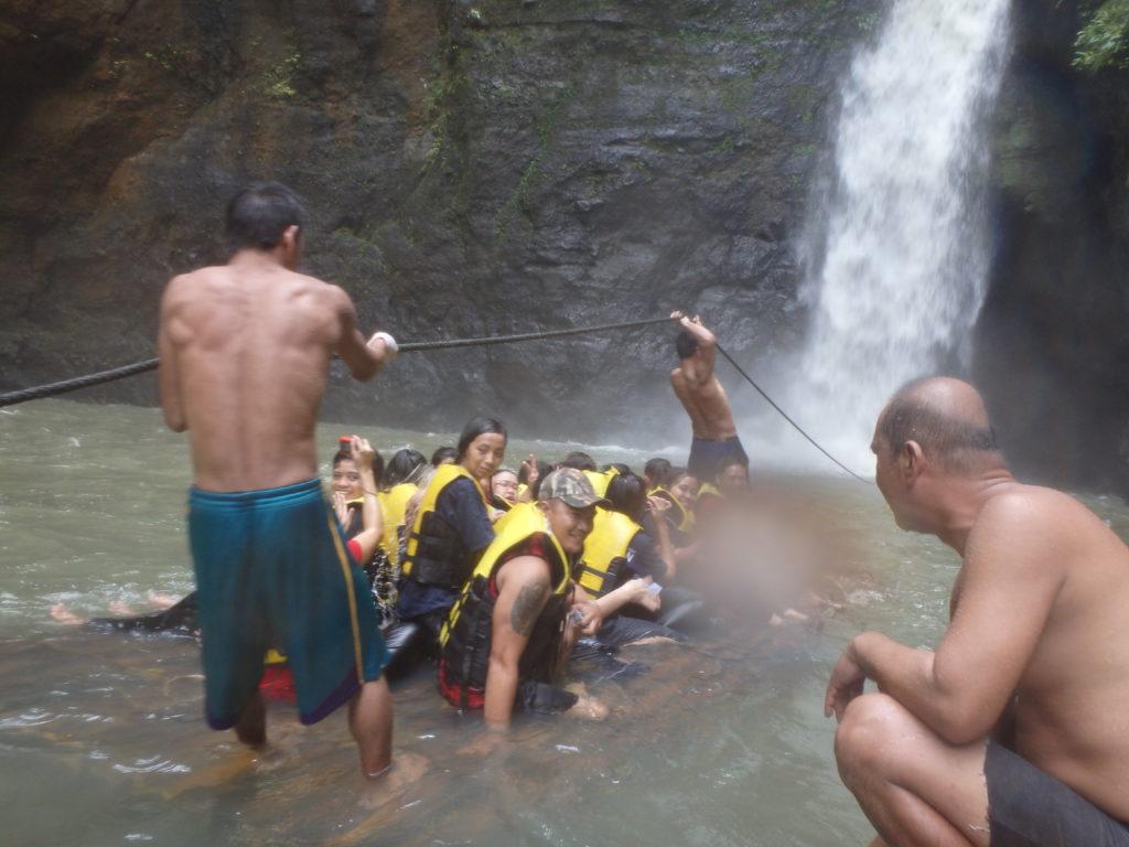 滝につっこむ直前のいかだの上の観光客たち