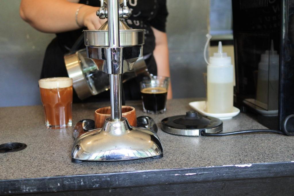グラスにブラックコーヒーを入れる店員