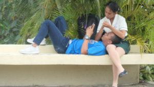 ベンチでたわむれる若いカップル